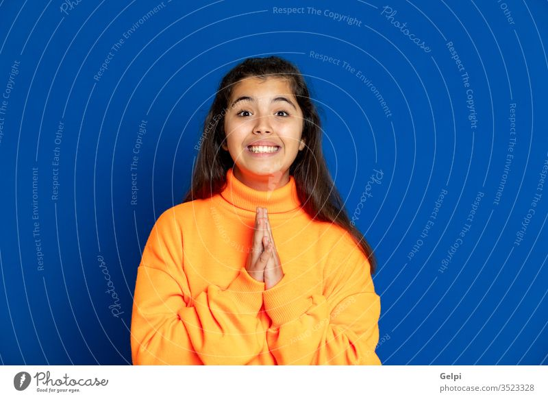 Preteen girl with yellow jersey preteen blue hand luck wish desire want pray religion meditation believe female people person pretty attractive background