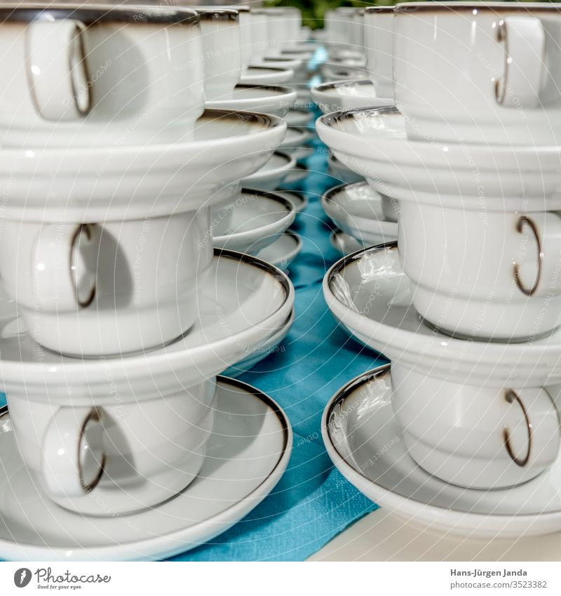 White coffee cups with plates stand stacked in a row Coffee cups mug white utensils drink celebration restaurant break cake pub enjoyment napkin blue cozy
