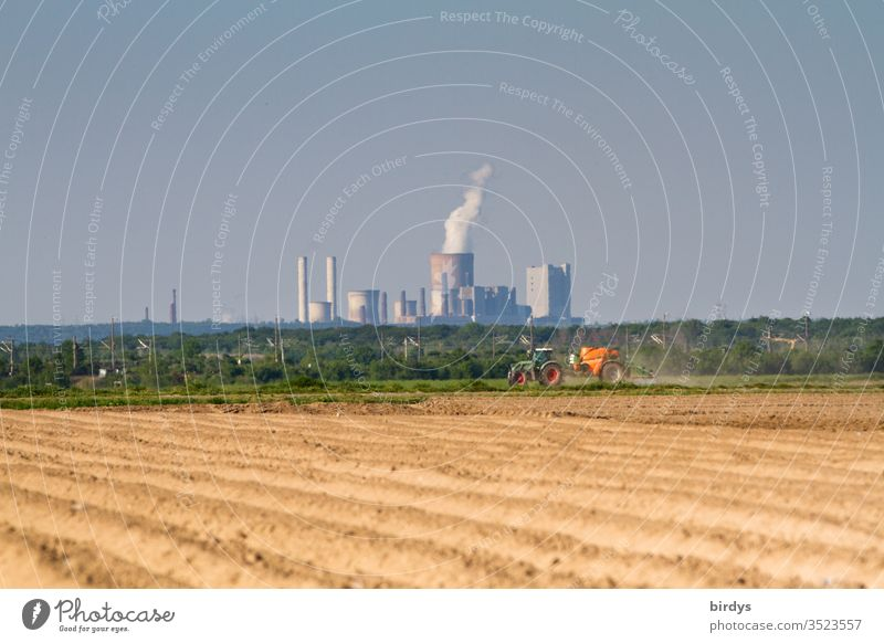 Lignite power station Niederaussem, in the foreground a farmer who applies pesticides to his field. Lignite power generation and conventional agriculture, responsible for climate change and pollution of the environment