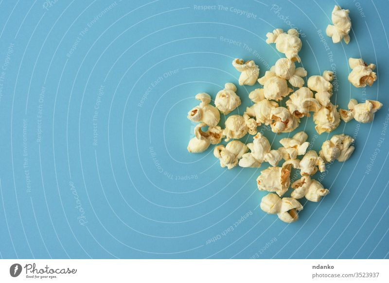 white delicious popcorn on a blue background, a place for an inscription overhead salt salted salty nutrition above classic closeup color crunchy eat fastfood