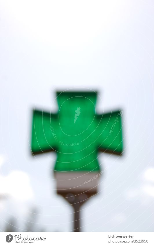 THE GREEN CROSS. Pharmacist symbol blurred in front of the sky Ocean green Sky Signal Pharmacy Green space transmitted transparent Translucent Clouds Summer