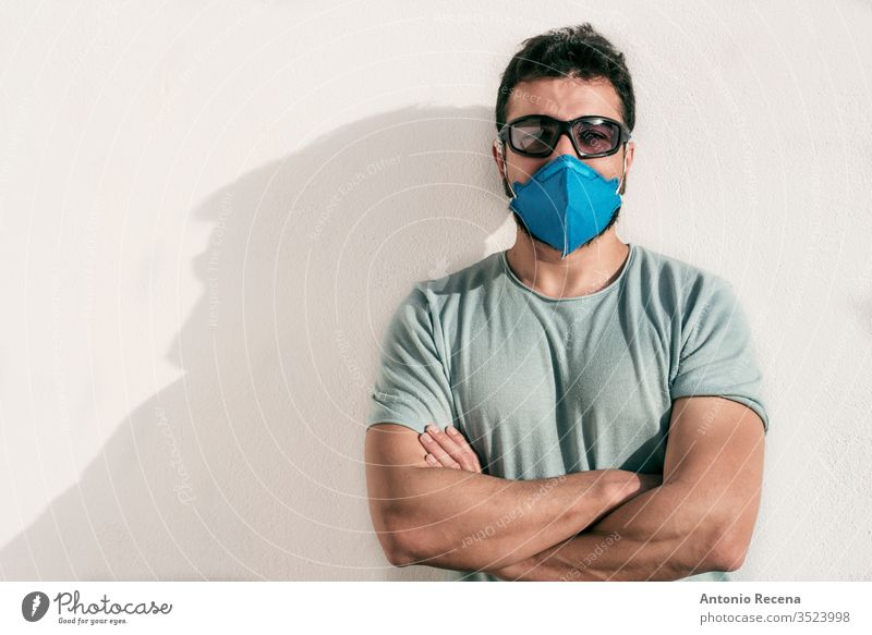 Man with facial mask and sunglasses looking at camera man corona virus allergy cool eyeglasses covid 19 contagion disease confinement pandemic protection