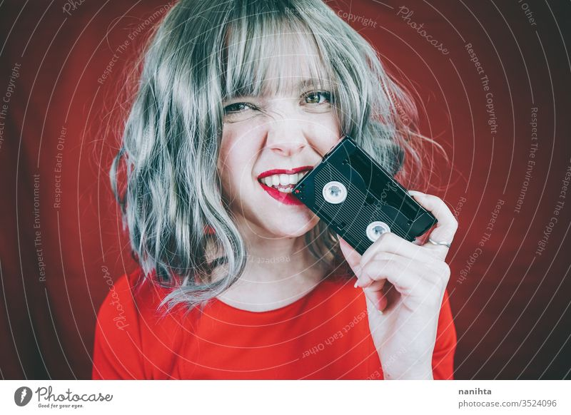 Artistic portrait with a model covering her face with a retro video tape vintage cassette red woman sexy pretty music culture 90s 80s decade old concept idea