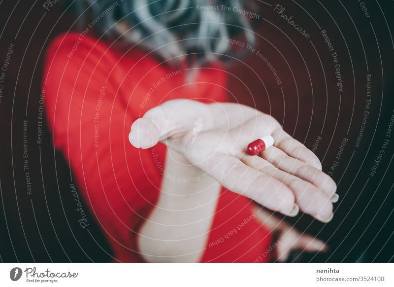 Young woman's hand holding a white and red pill drug medicine virus addict addictive addiction painkiller pain killers close up bokeh closeup blur focus macro