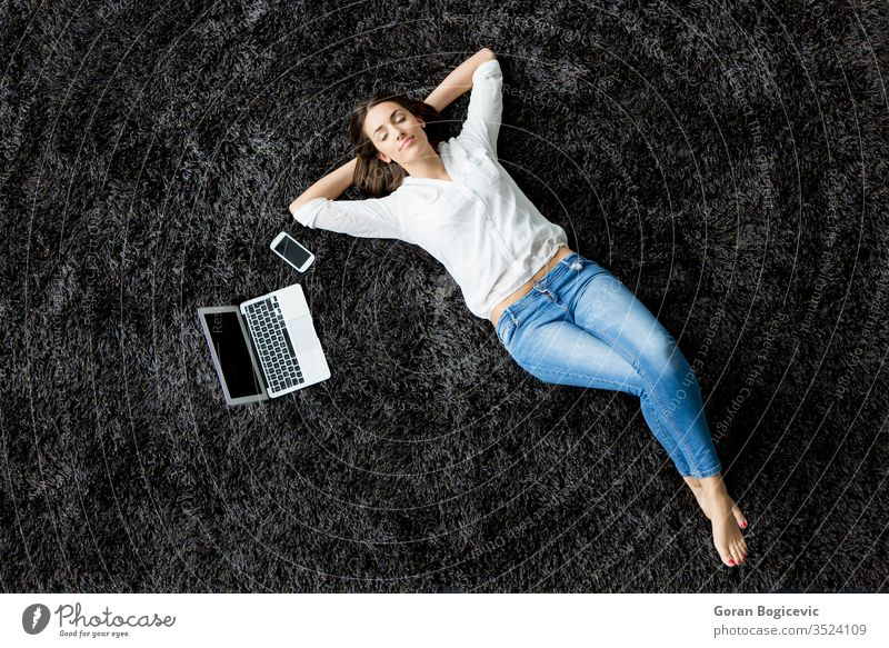 Young woman laying on the carpet back laptop floor girl phone charming leisure view red european adult people caucasian female computer modern lifestyle young