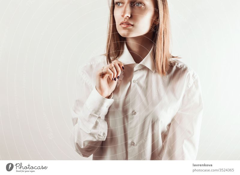 Portrait of young adult woman holding collar of white shirt with her hand, selective focus look clean skin natural makeup manicure rings jewelry studio bracelet