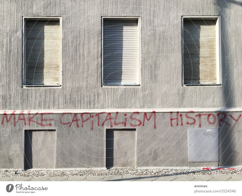 Grey house wall with closed shutters and inscription Gray Capitalism Make capitalism history Criticism Facade saying slogan Wall (building) Deserted