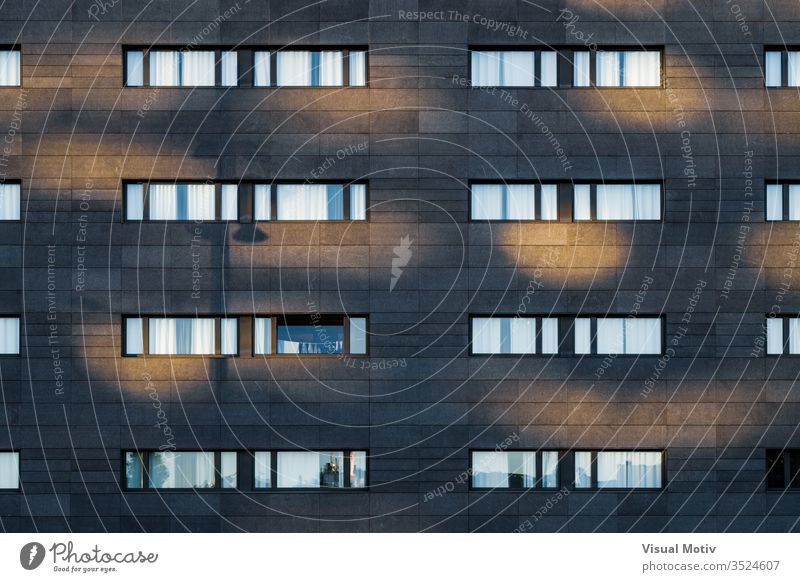 Afternoon light over the black facade of an urban building with long horizontal windows rows structure Architecture abstract building facade urban facade color