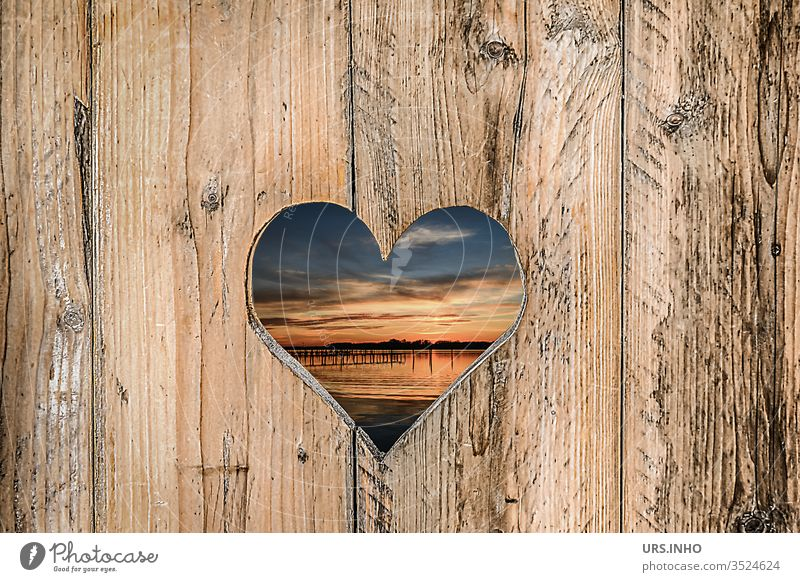 sawn out heart in a wooden board wall with view to the sunset at the lake Heart boards Sawn Sunset Vista Wooden board wall Wooden boards cute structure