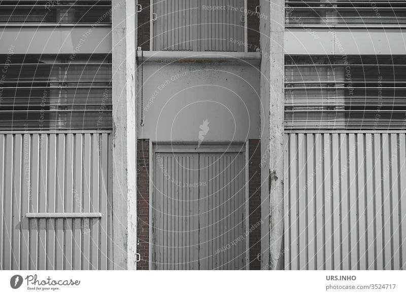 grey facade of a warehouse Warehouse Facade Architecture Factory built Industrial plant door Stripe Window Storage shed store Gray symmetric Symmetry