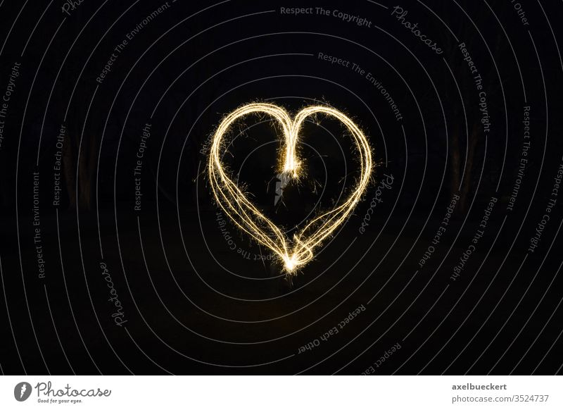 heart shape light painting with sparklers painting with light love symbol fire sign sparks fireworks glow romance romantic dark night outside black valentine