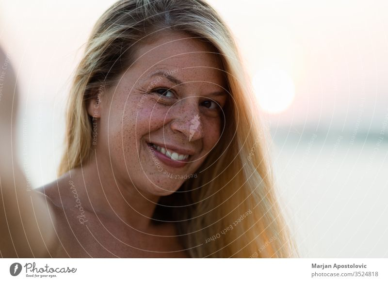 Young tanned woman taking a selfie in sunset adult attractive beach beautiful beauty blonde camera carefree casual caucasian cheerful complexion cute enjoying