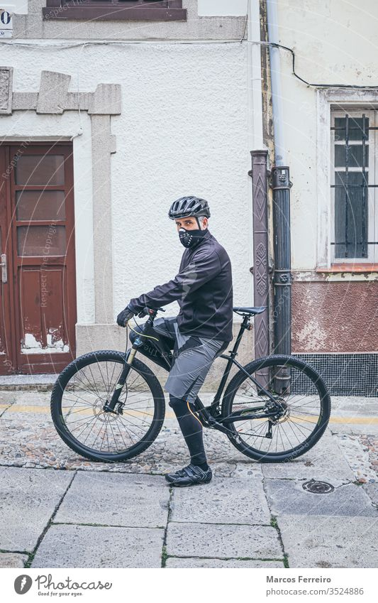 adult man with bike in the city with mask sport viruses corona-virus respiratory face mask outside covid caucasian healthcare covid 19 prevention people