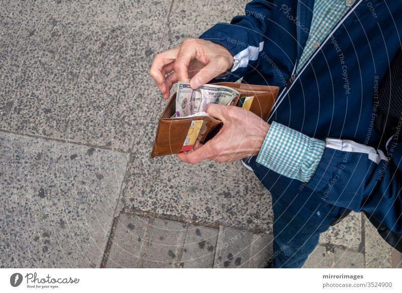 man opeing up his wallet to spend some amercan currency cash paper money business and finance making cash payment economic and payments spending capital