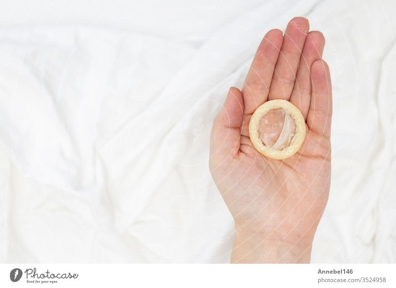 Safe sex concept. Hand holding a condom with white sheets blanket background hand protection aids healthy control contraception contraceptive hiv man safe