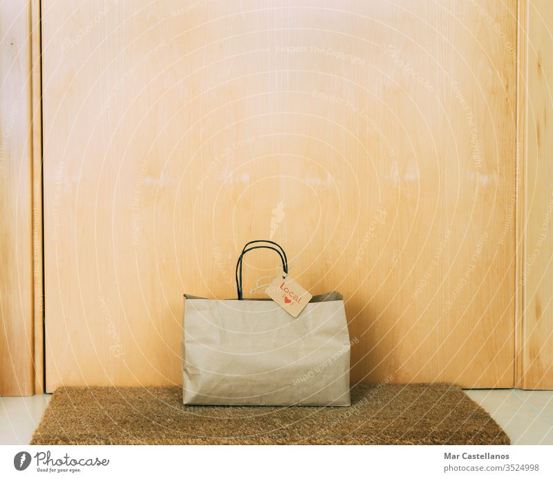 Paper shopping bag with cardboard label on the front door of the house. Concept of shopping. paper entrance mat recyclable sales local trade reusable copy space