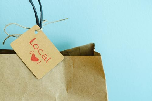 Paper shopping bag on a blue background. Label with heart and text LOCAL. Shopping concept. paper label recyclable sales local trade cardboard reusable