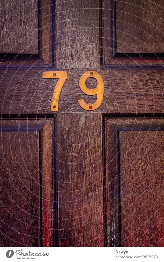 House number 79 on a dark wooden front door 79 number address aged britain classic classy close up closeup decoration design detail digit digits elegance
