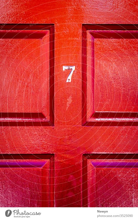 House number 7 on a lucky red wooden front door 7 number address britain burgundy classic classy close up closeup copy space copyspae decoration design detail