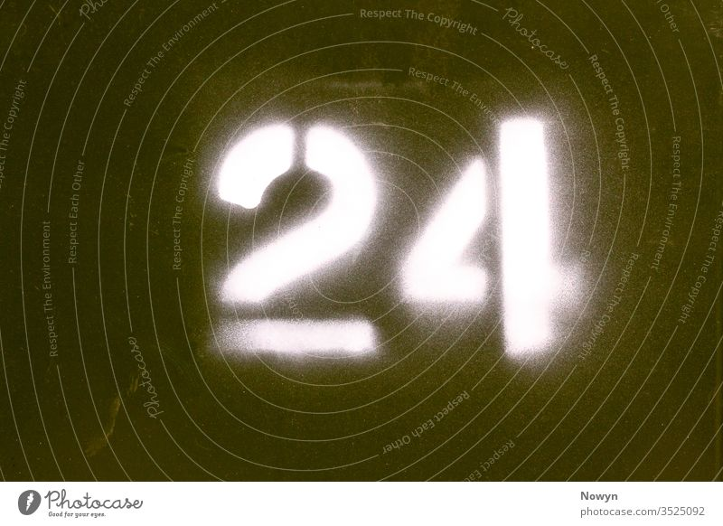 Number 24 spray painted onto a military green metal surface 24 number army britain close up closeup detail digit digits door exterior figure house house number