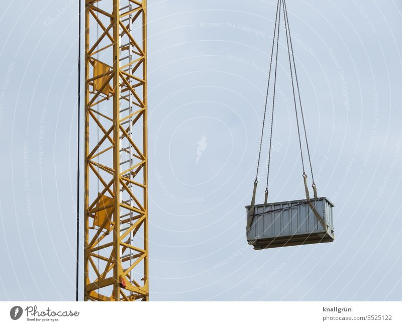 Yellow construction crane with a medium-sized grey metal container suspended from chains on the jib Crane Container hang Construction site Construction crane