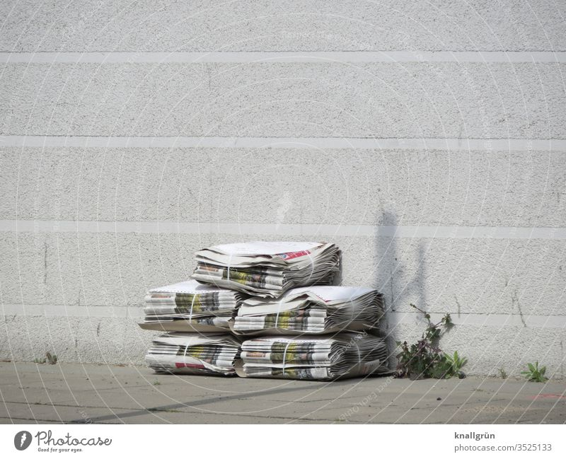 Five packs of newspapers stacked on the sidewalk in front of a white house wall, next to them some weeds growing out of a joint Newspaper Print media Stack