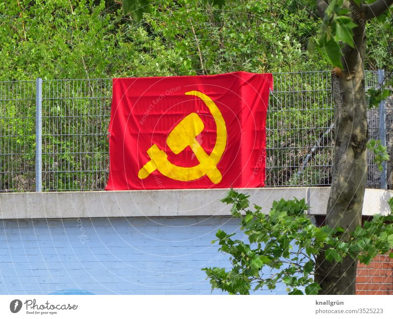 Large hammer and sickle flag attached to a metal fence above a wall Soviet Union Flag Hammer Red Yellow Communism Politics and state Symbols and metaphors