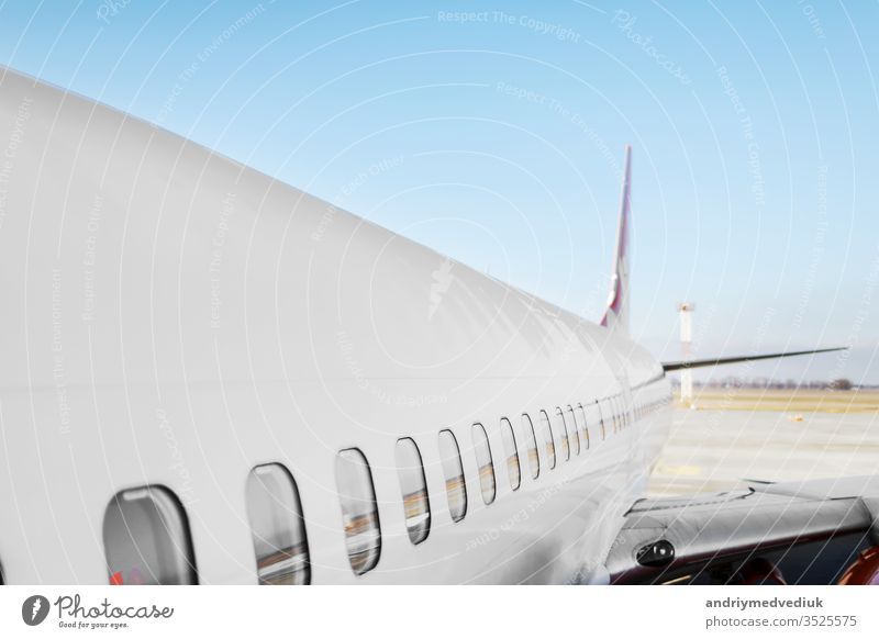 Aircraft porthole - side window airplain. White heavy passenger jet engine airplane on runway at airport against blue sky aviation transportation theme background.