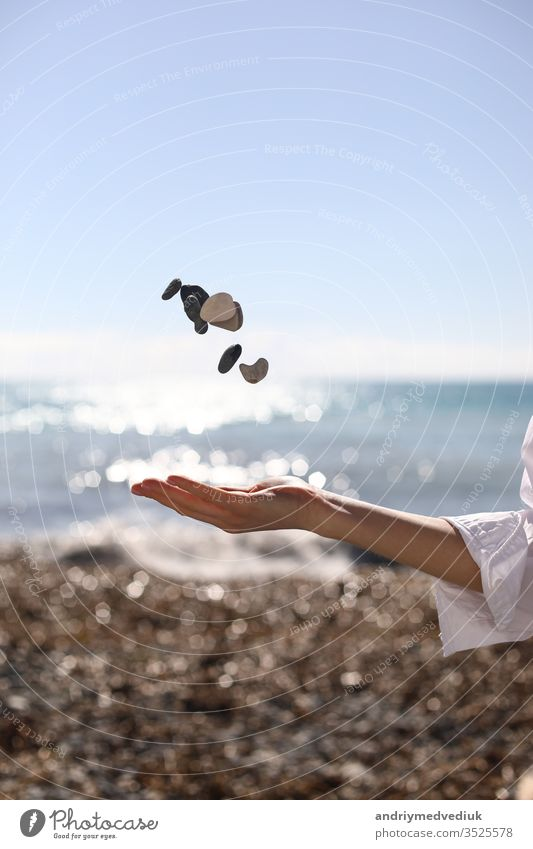 female hand throws a pebble in her hand against the background of the blue sky, beach and sea. place for text. girl young nature summer beauty travel people
