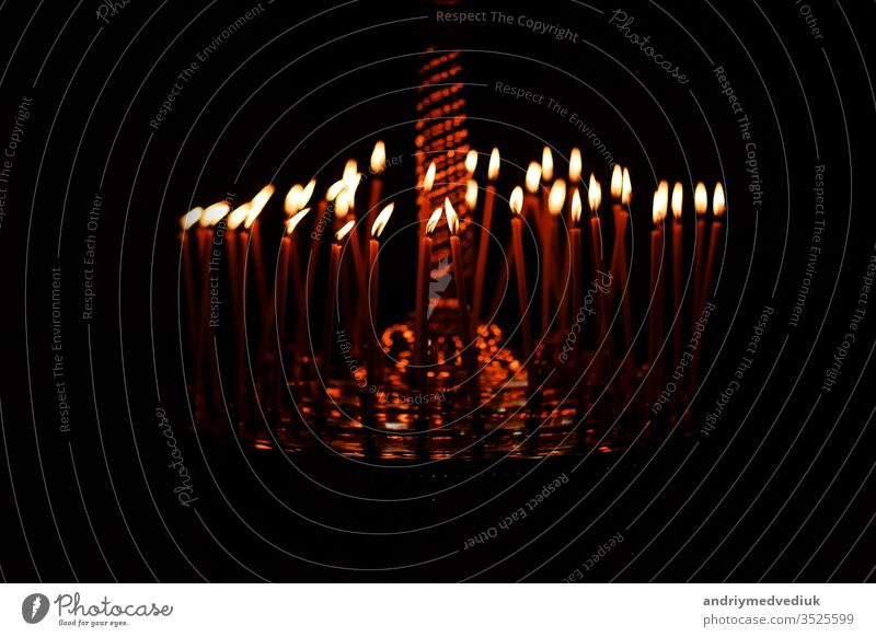 Many candles burning at night on the black background in church. Candle flame set isolated in black background. Group of burning candles in dark candlelight wax