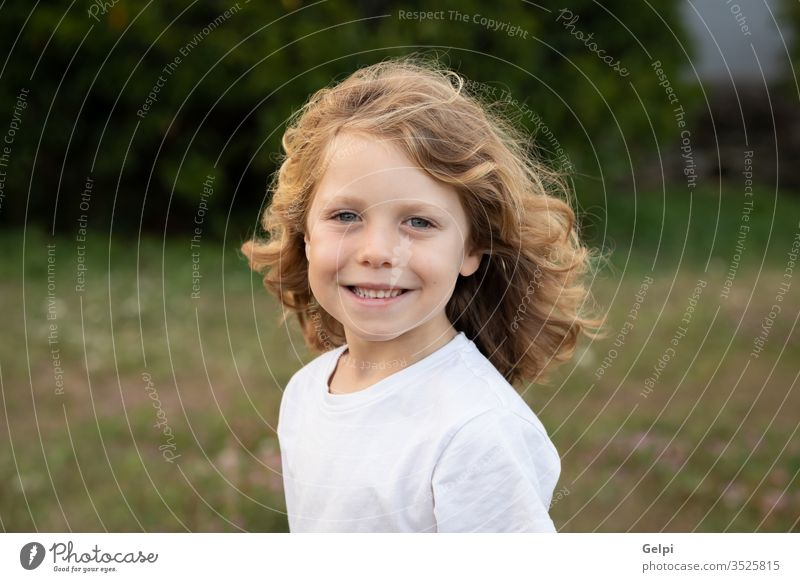 Funny blond kid with long hair child outside one childhood people caucasian joy boy little nature wavy play summer young outdoor fun happy playful lifestyle