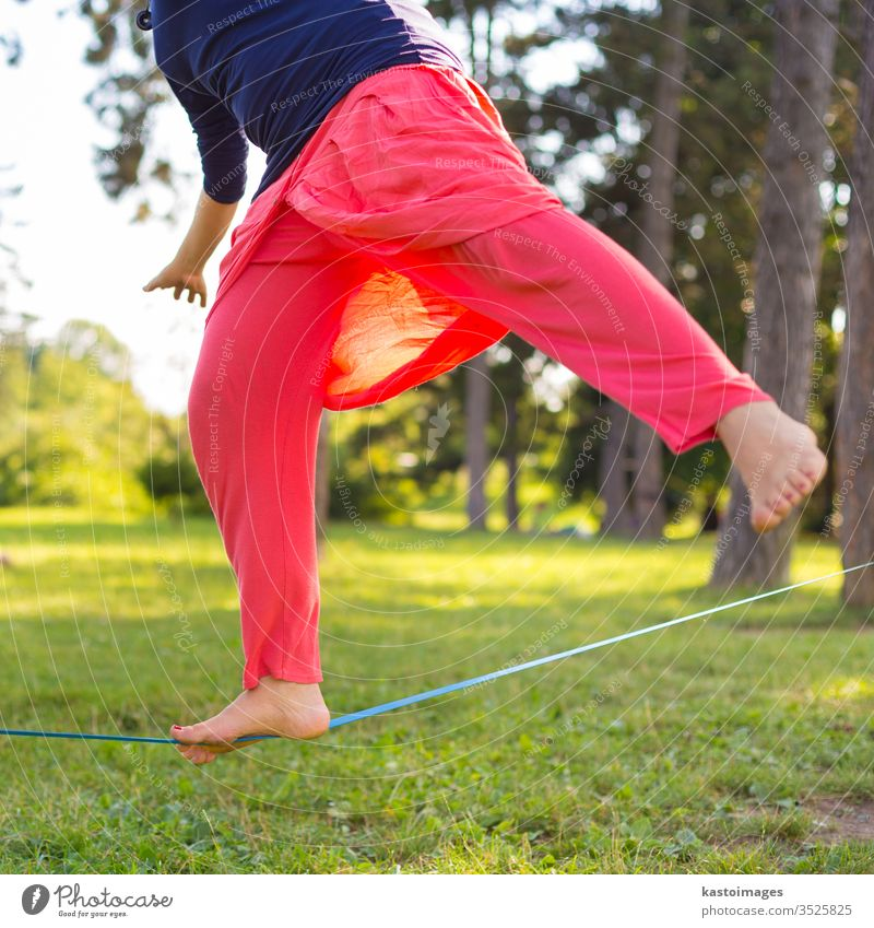 Slack line in the city park. slack line slackline activity sport balance tightrope young person fitness back nature concentration walking outdoors skill one