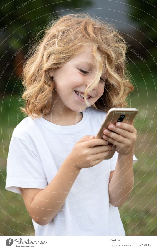Funny child with long hair holding a mobile phone park leisure cellphone childhood smartphone lifestyle boy blond communication connection casual clothing