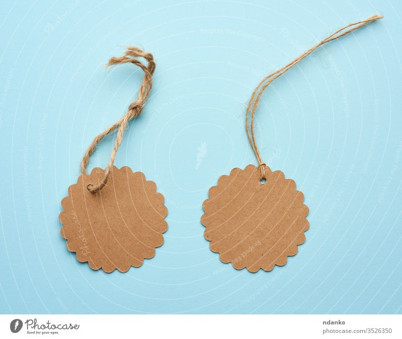 Round empty brown paper tag tied with string price pricing recycled blue address background blank business buy card cardboard cord coupon craft design discount