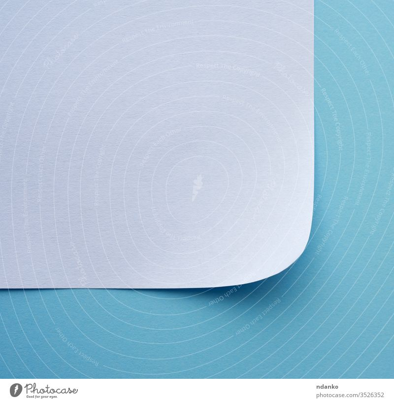 wrapped sheet of white paper on a blue background corner page blank curl edge document note texture frame space empty folded turn message design office clean
