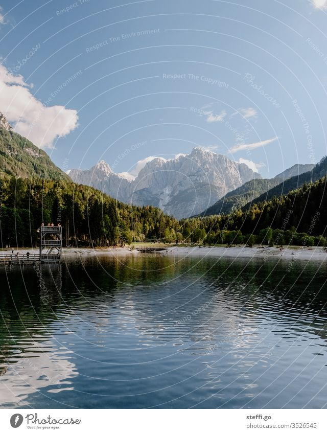 Lake surrounded by mountains in summer Mountain range Destination Far-off places Lakeside Summer Trip Calm Rock Freedom Hiking Relaxation Clouds Tourism