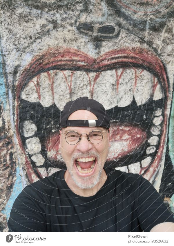 A screaming man in front of a graffiti Man Adults Human being Facial hair Head Masculine Eyeglasses Face Looking into the camera Graffiti
