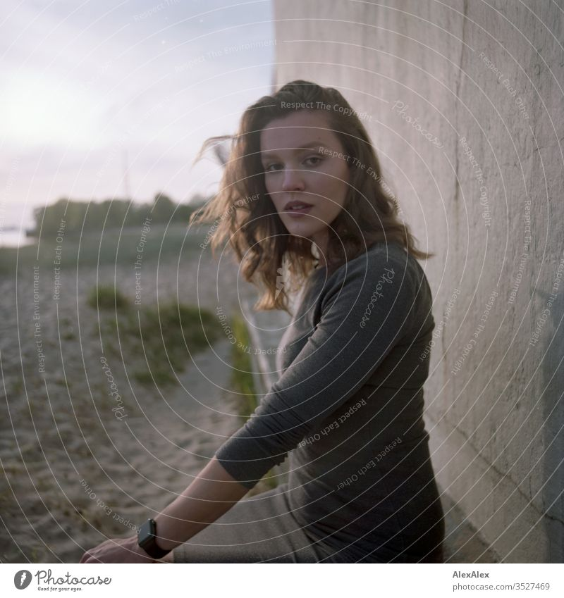 analogue portrait of a young woman in a dress in front of a wall Woman girl already great Athletic Slim fit brunette Curl long hair Wall (building) Concrete