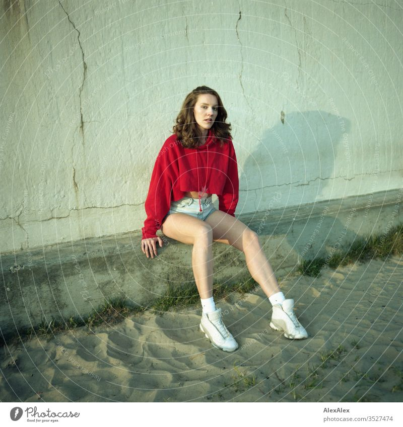 analogue portrait of a young woman with red hoodie and hot pants Woman girl already great Athletic Slim fit brunette Red Hot pants Curl long hair sneakers Legs
