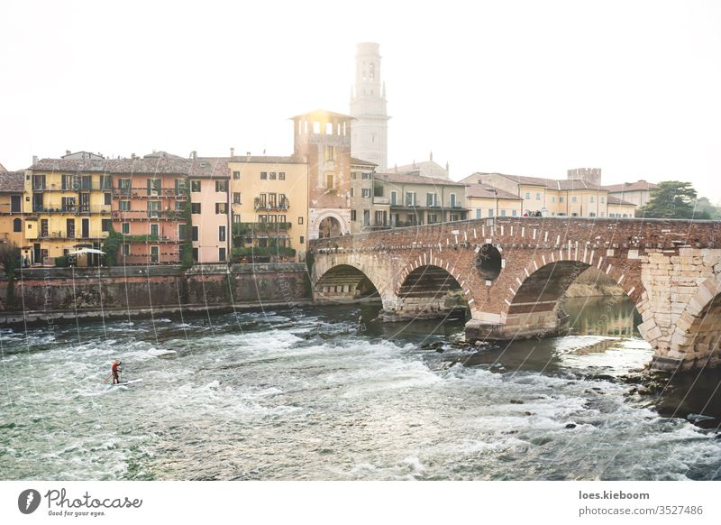 River surfer during sunset with city view at Ponte Pietra in Verona, Italy verona sport italian tower building ponte pietra bridge europe travel italy