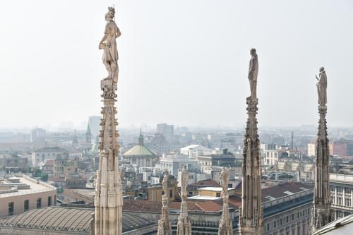 Statues of the dome looking over the cityscape of Milan, Italy on a sunny day cathedral italy architecture milan aerial panoramic view urban skyline landmark