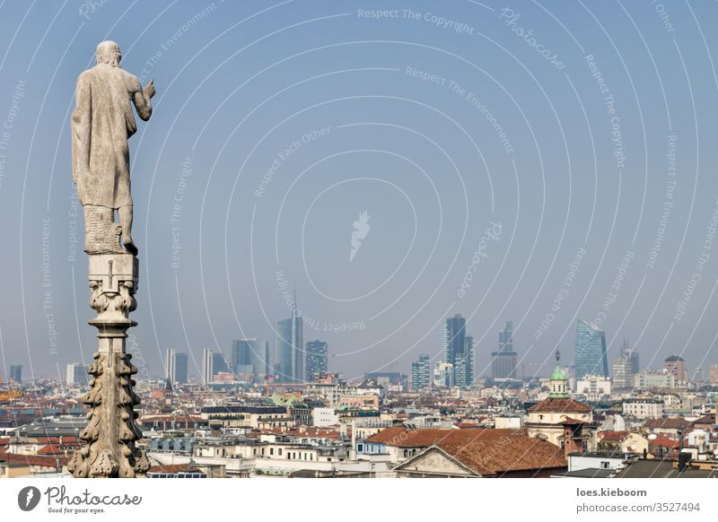 Statue of the dome looking over the modern cityscape of Milan, Italy on a sunny day cathedral italy architecture milan aerial panoramic view urban skyline