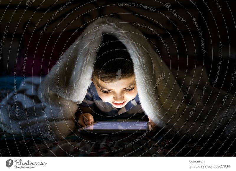 Little child using a tablet covered with a blanket alone application bed bedroom bedtime boy childhood children only children playing communication computer
