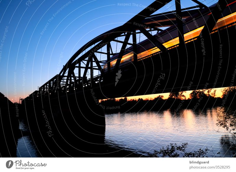 The last night train begins its long journey. Train with illuminated windows crosses the Main in Hanau at sunset on the Steinheim Bridge Railroad Rail transport