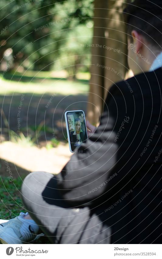 Back view of a young teenage student sitting on campus while using a mobile phone person technology lifestyle smartphone communication teenager holding outdoor