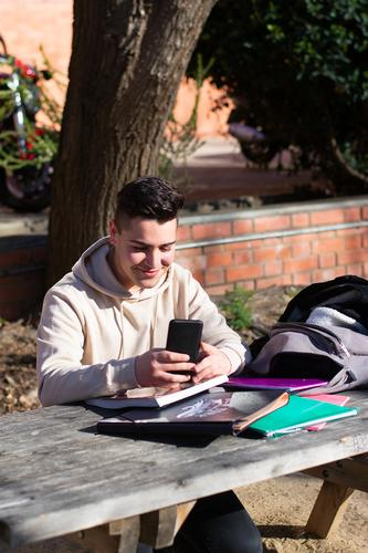 Young student sitting in a park while using a mobile phone on a wooden table one person communication technology education computer notebook studying internet