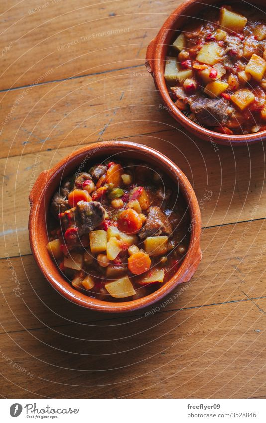 potatoes and meat stew on a clay container cuisine gravy burgundy dinner sauce bowl bell pepper rustic plate beverage wine onion meal galician beef wood cook
