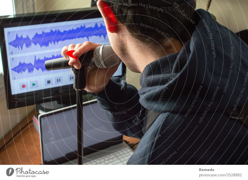 Back view of a man singing in a microphone and recording the audio to make a song at home. Amateur musician singing and playing guitar. quarantine coronavirus