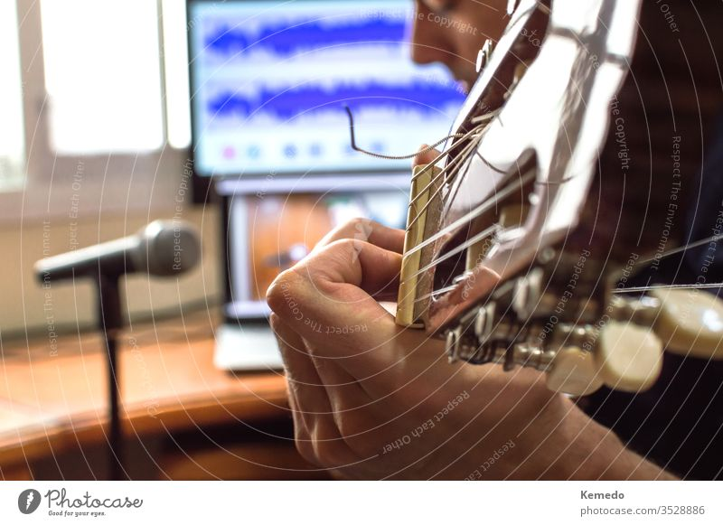 Person playing guitar and recording the audio using microphone and technology at home. Amateur musician recording music. hand man close up blur enjoy focus