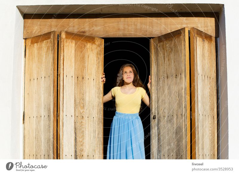 woman leaning out the door wanting to go outside during the quarantine by the covid-19 gate access entrance nostalgically waiting to get out wooden door